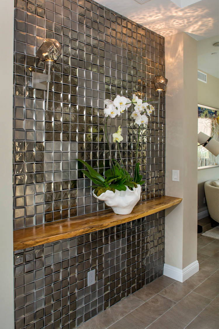 Home entry with glass tile on wall and wooden shelf.