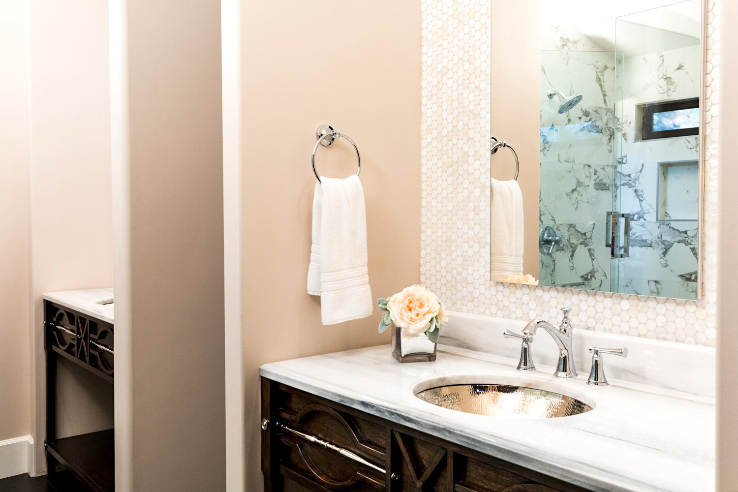 Master bath with wood and silver vanity cabinet, Marble top, silver metal sink.