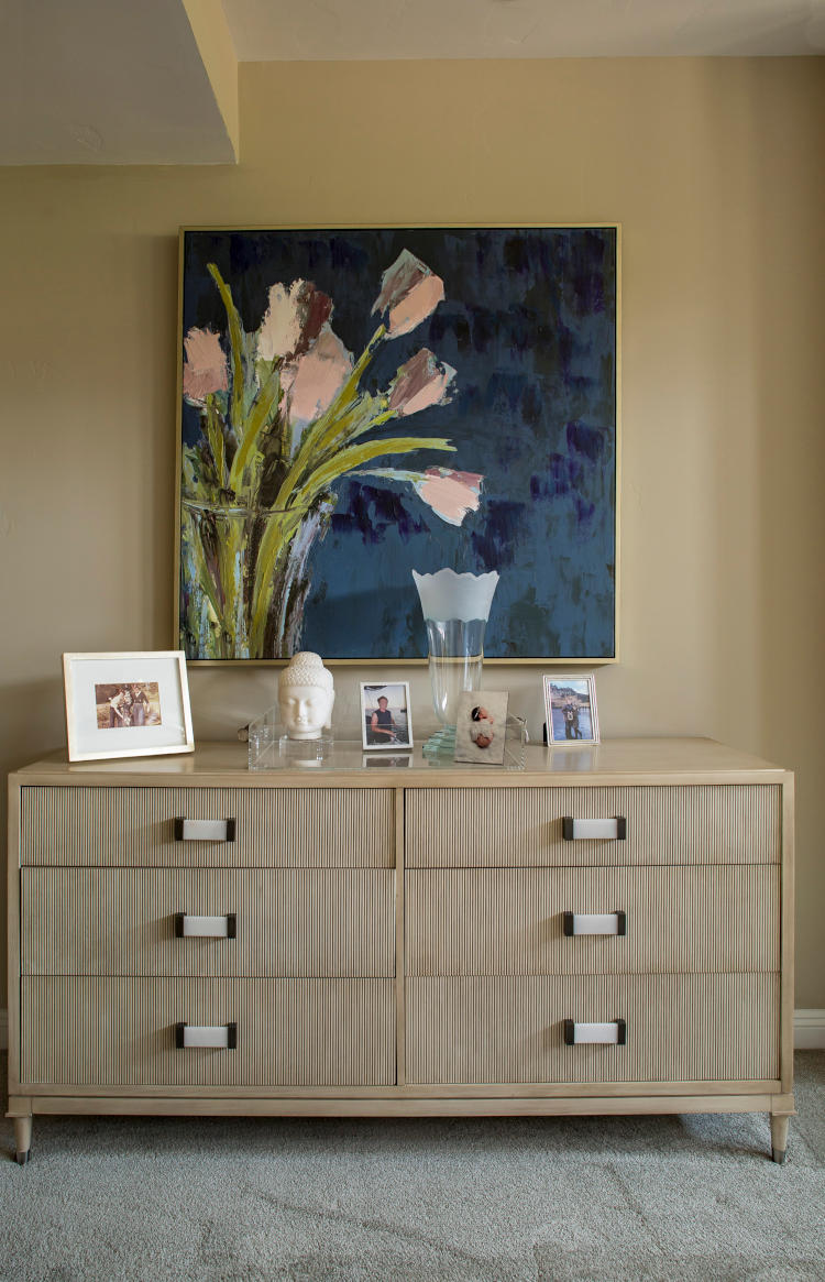 Bedroom cabinet with drawers and art peice / picture hanging on top.