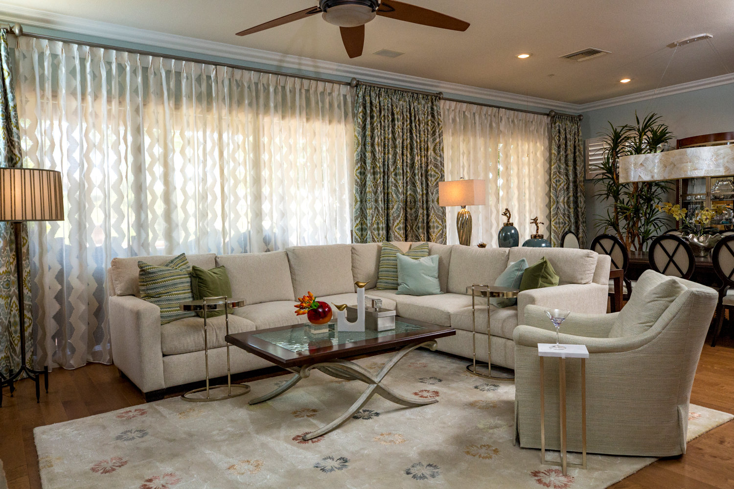 Bright, traditionally styled family room, cream colored sectional, colorful drapes with sheers.