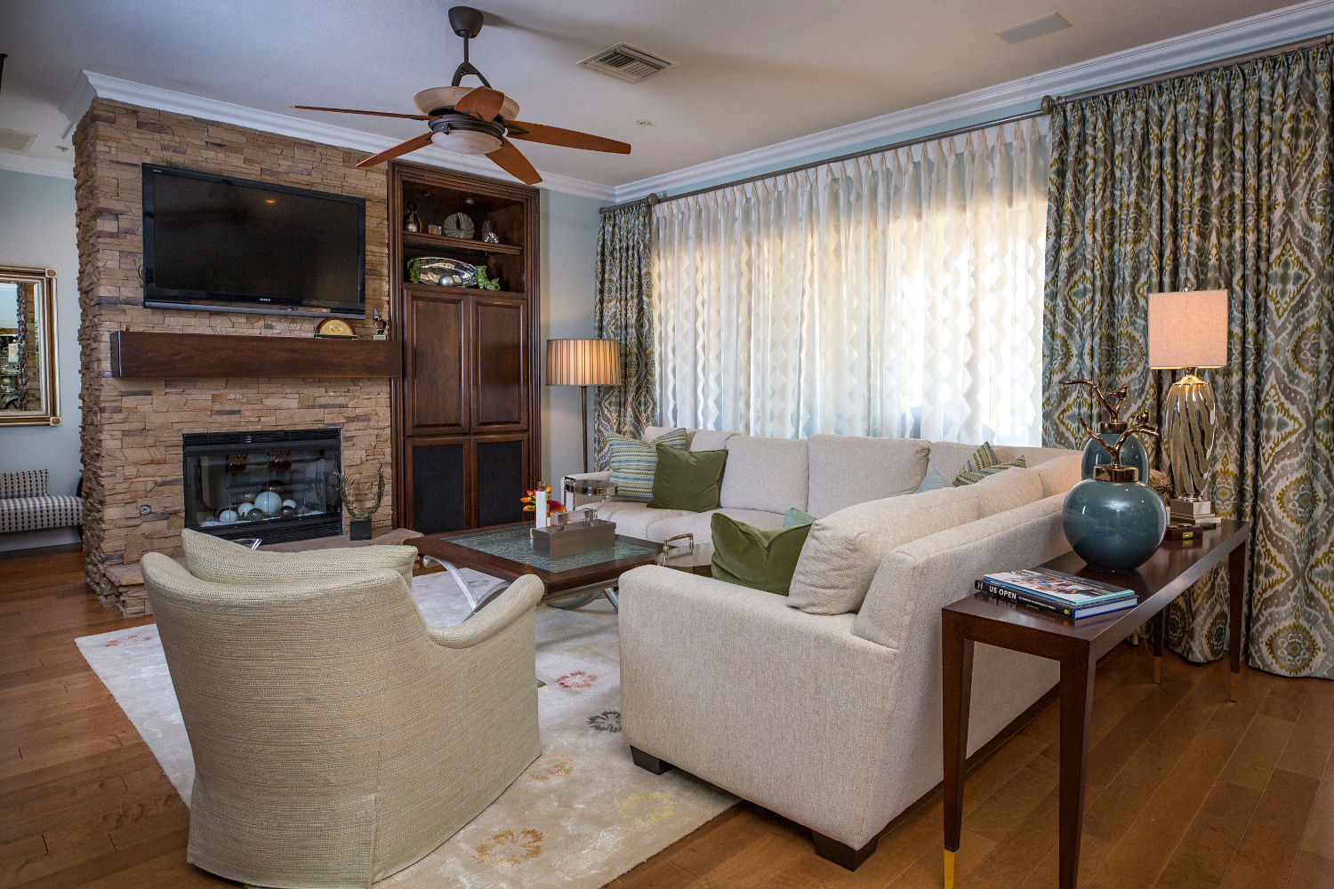 Bright, traditionally styled family room, stacked stone fireplace with wood mantel.