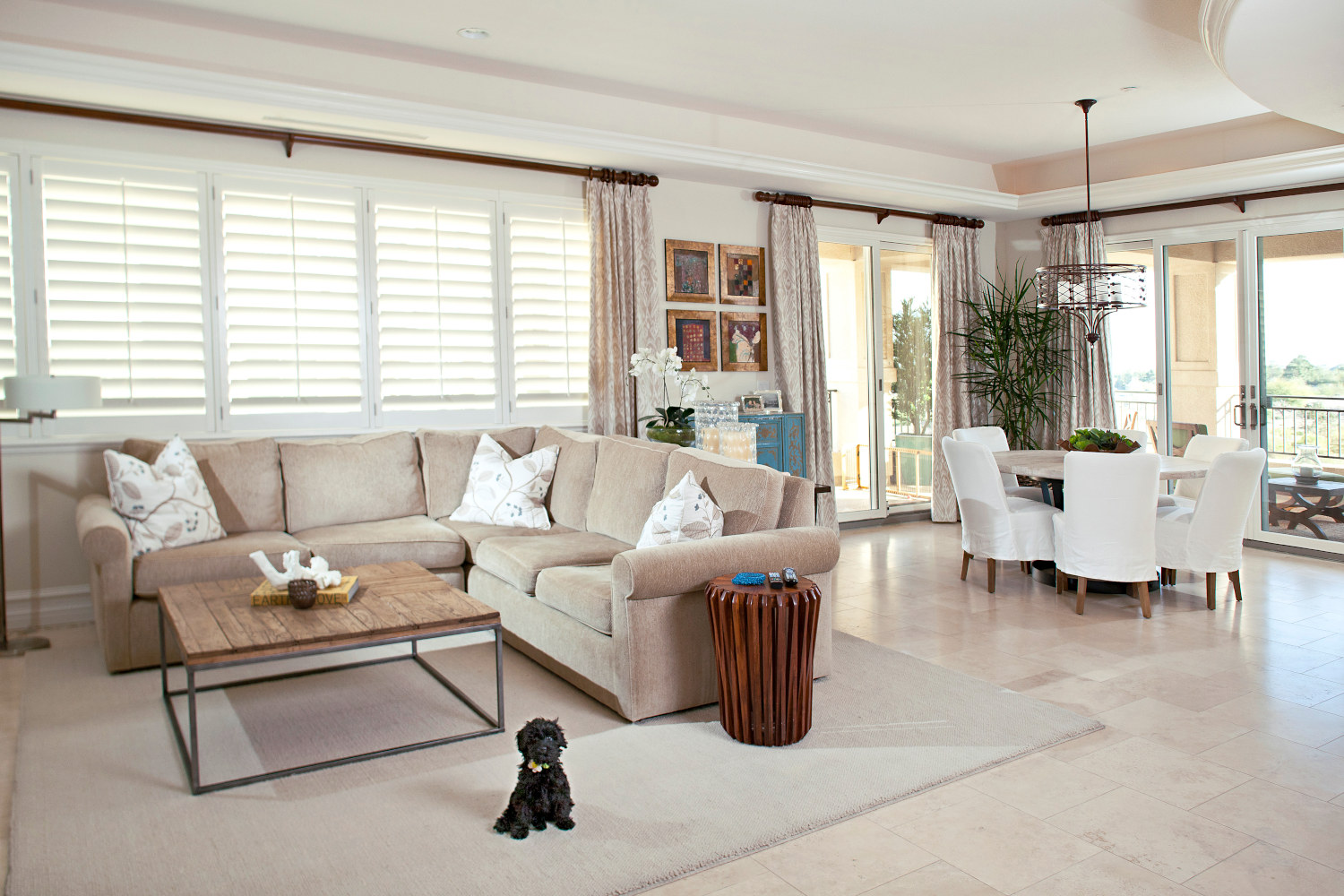 Open space bright family room and dining room combo, with cream travertine flooring.