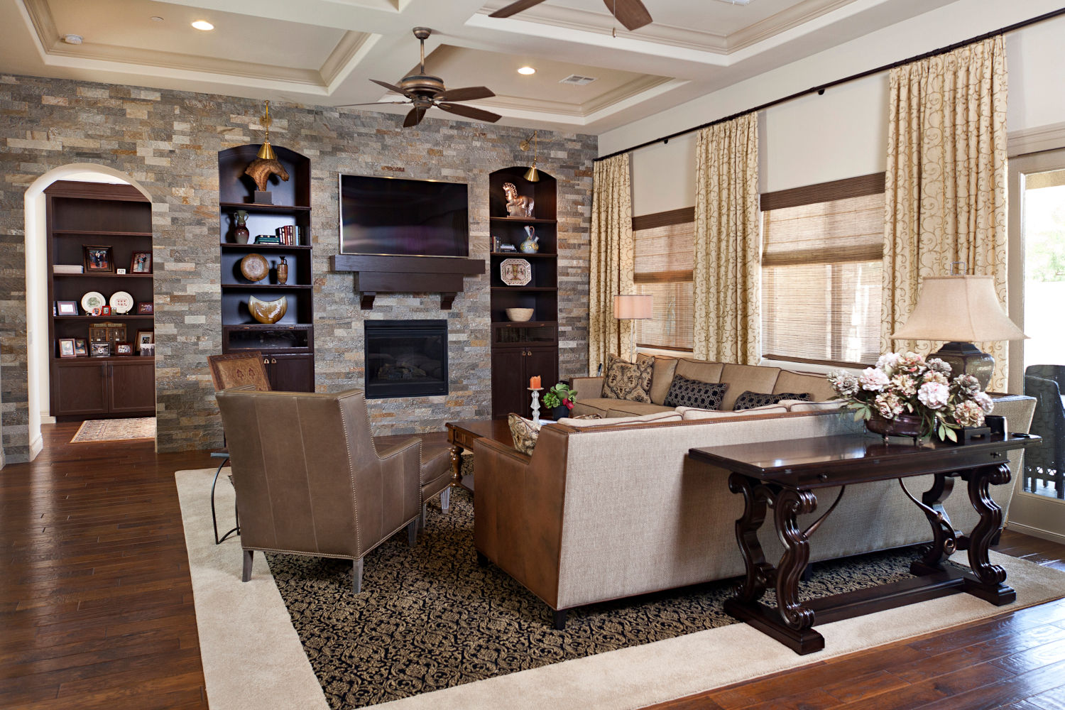Traditional family room with stacked stone wall, bookcases, wood floor, leather furniture.