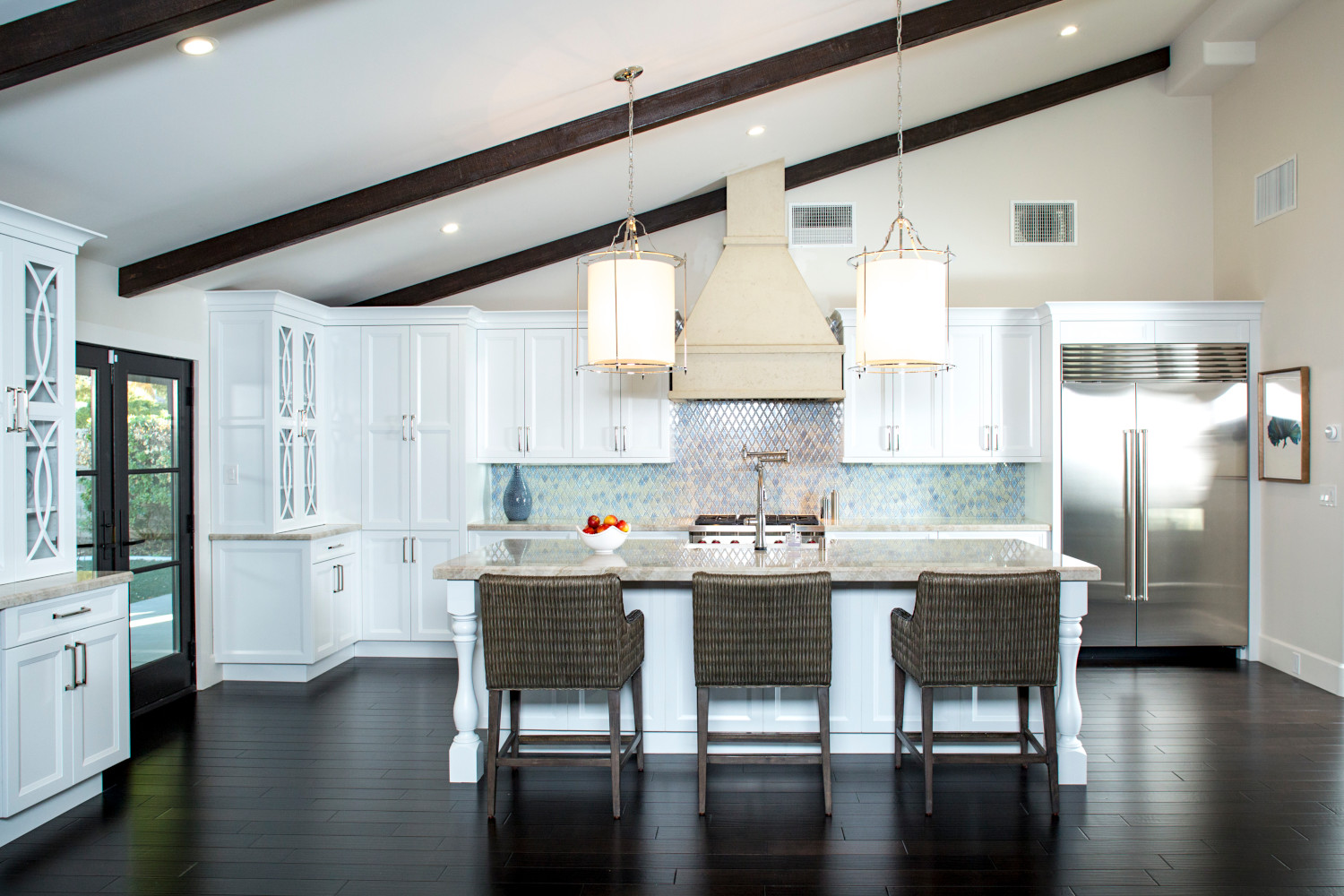 Santa Barbara styled white kitchen, wood ceiling beams, large island with woven reed counter stools.