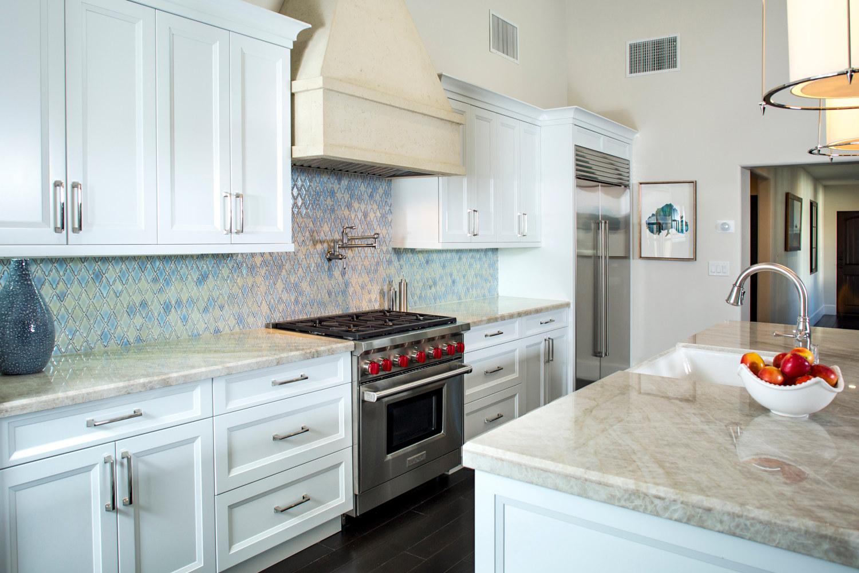 White Santa Barbara styled kitchen, blue tile backsplash, Wolf appliances, beige quartzite