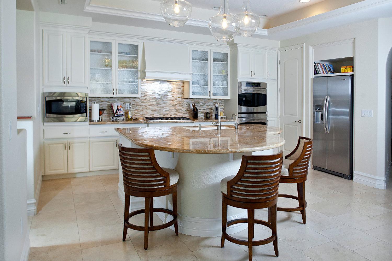 Traditional kitchen, white cabinets, travertine countertops, glass backsplash, wood counter stools.