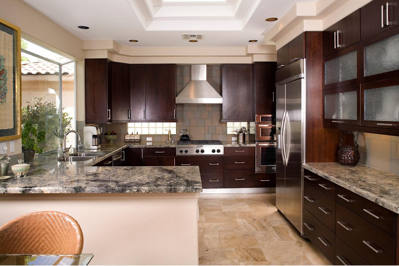 Contemporary espresso kitchen with glass tile backsplash, granite countertops, cream colored walls.