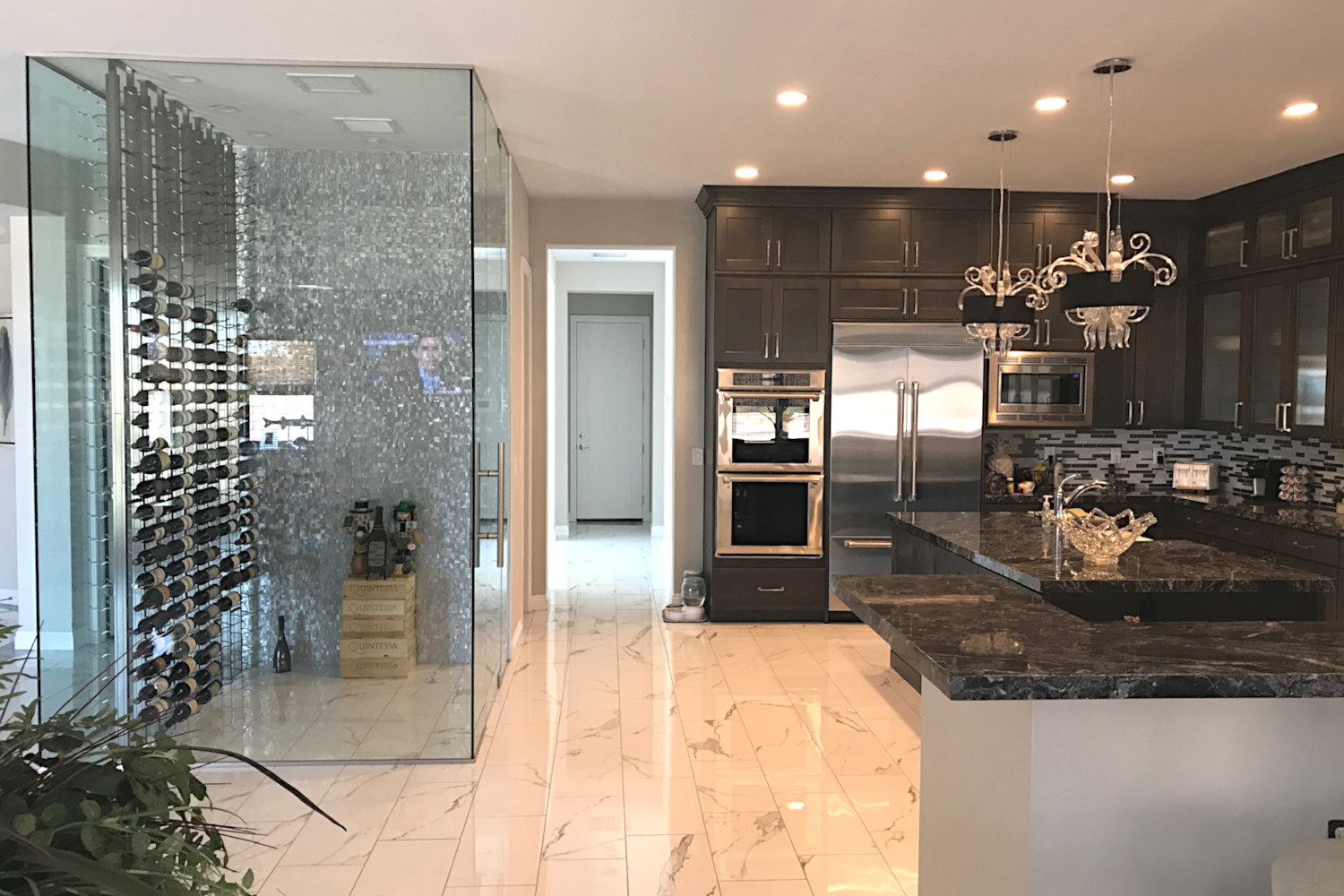 kitchen with dark cabinets, black grnite countertops, walk-in glass wine cooler,  polished floor.