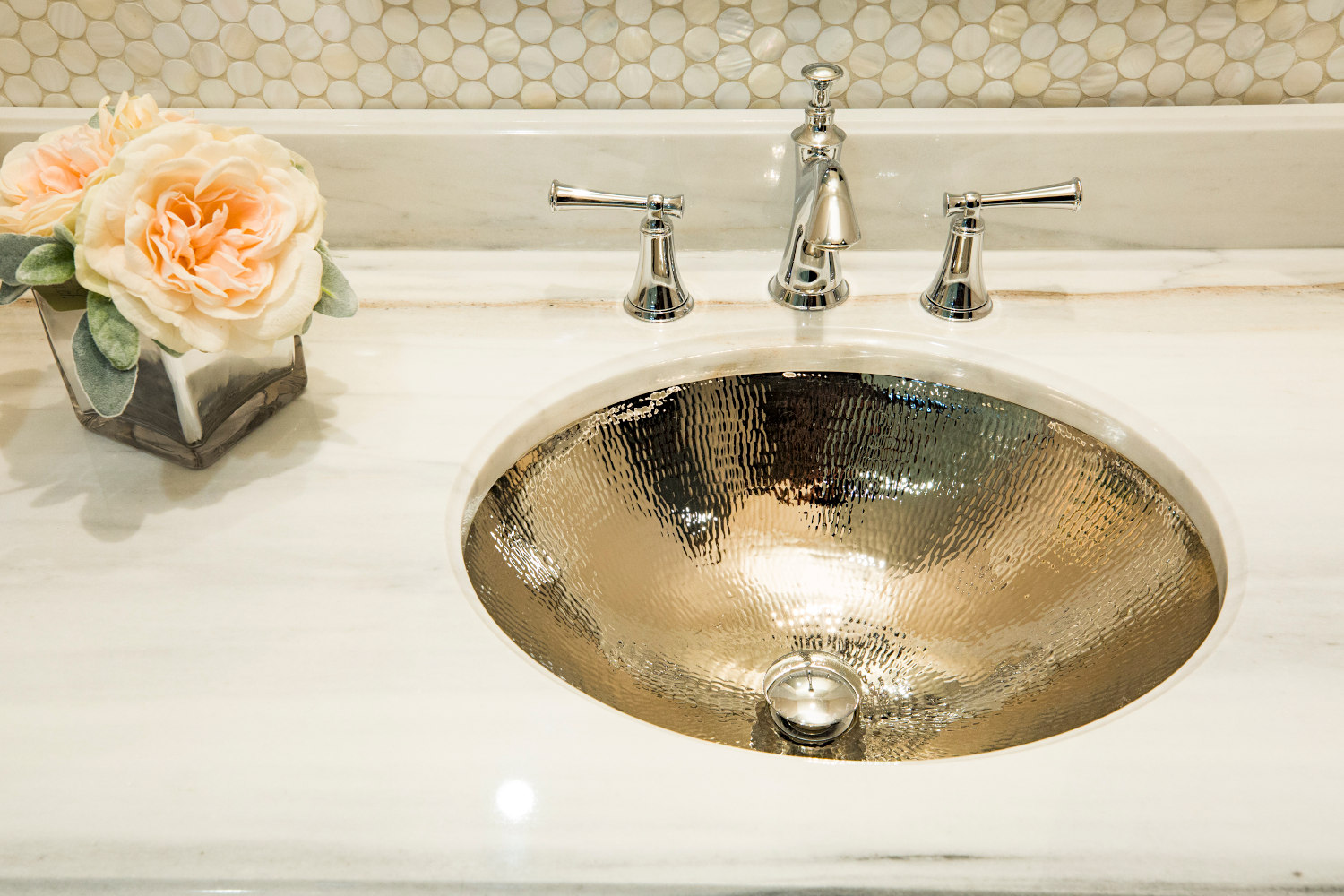Master bath marble top vanity with silver hand hammered metal sink.