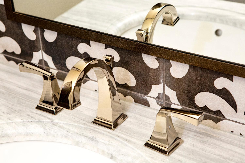 Polished nickel bathroom faucet with marble top vanity Tuscan style brown tile backsplash.