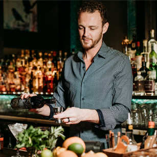 smiling male bartender making a cocktail with spirits in the background | The Raven Room