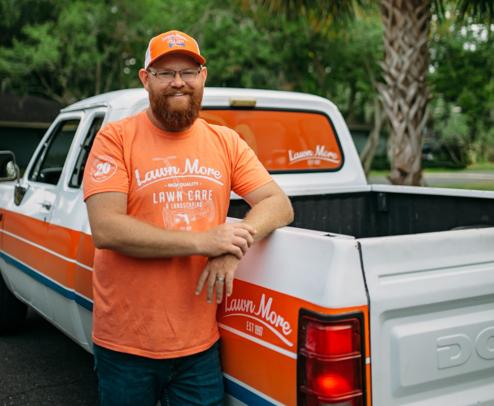 Jonathan the owner of LawnMore smiling in front of a branded truck