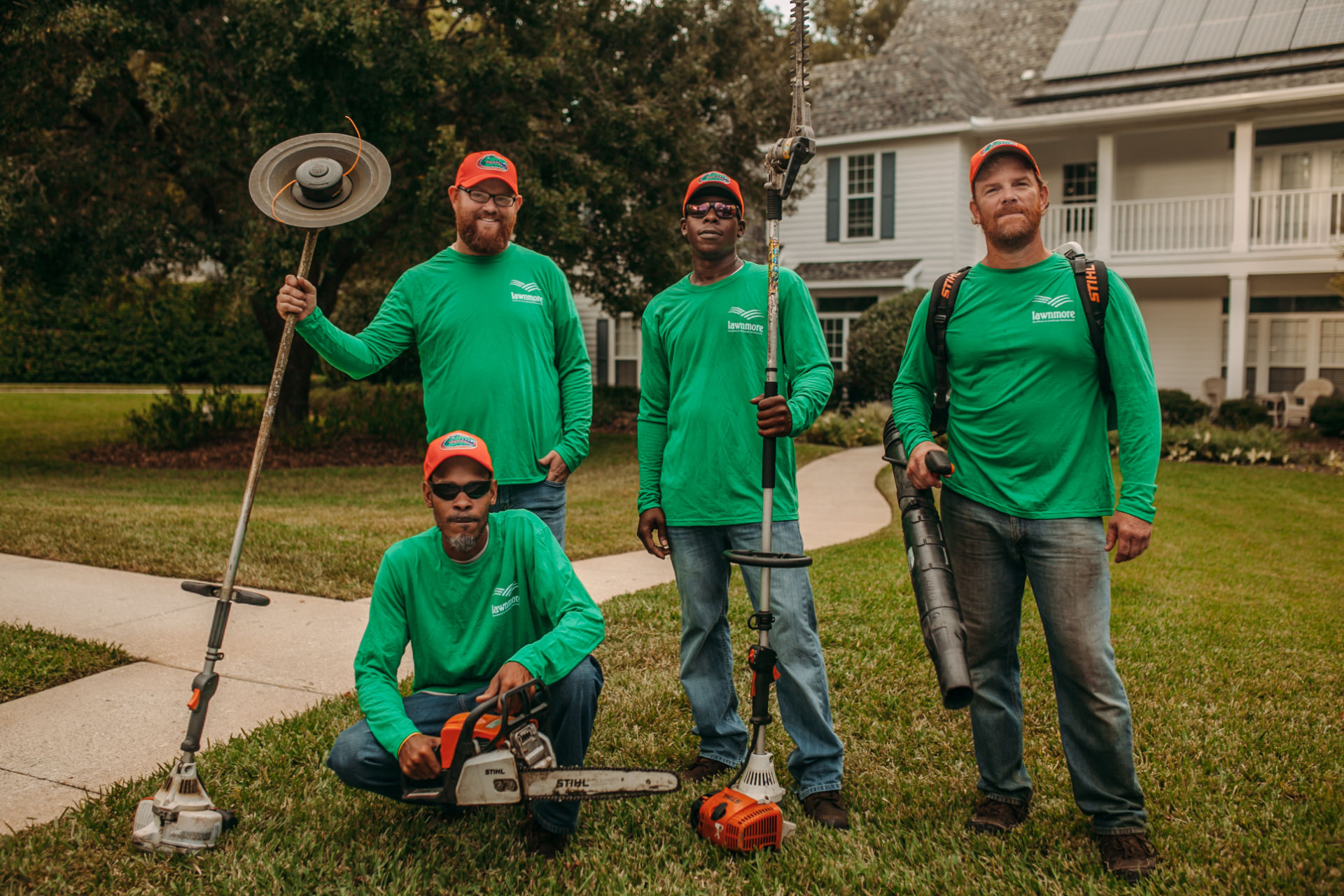 LawnMore crew members with mowing equipment smiling for a group photo