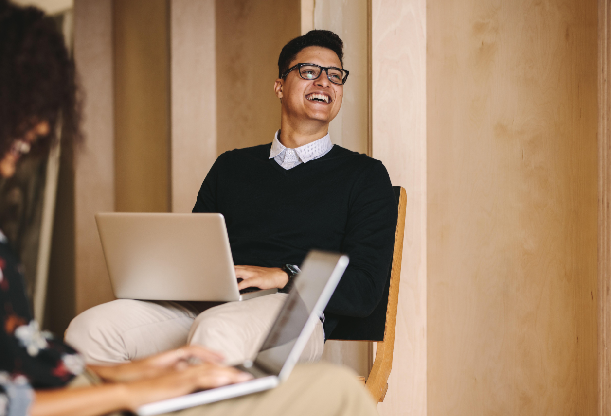 A happy man in a nice sweater with glasses sitting and holding a laptop in a professional setting