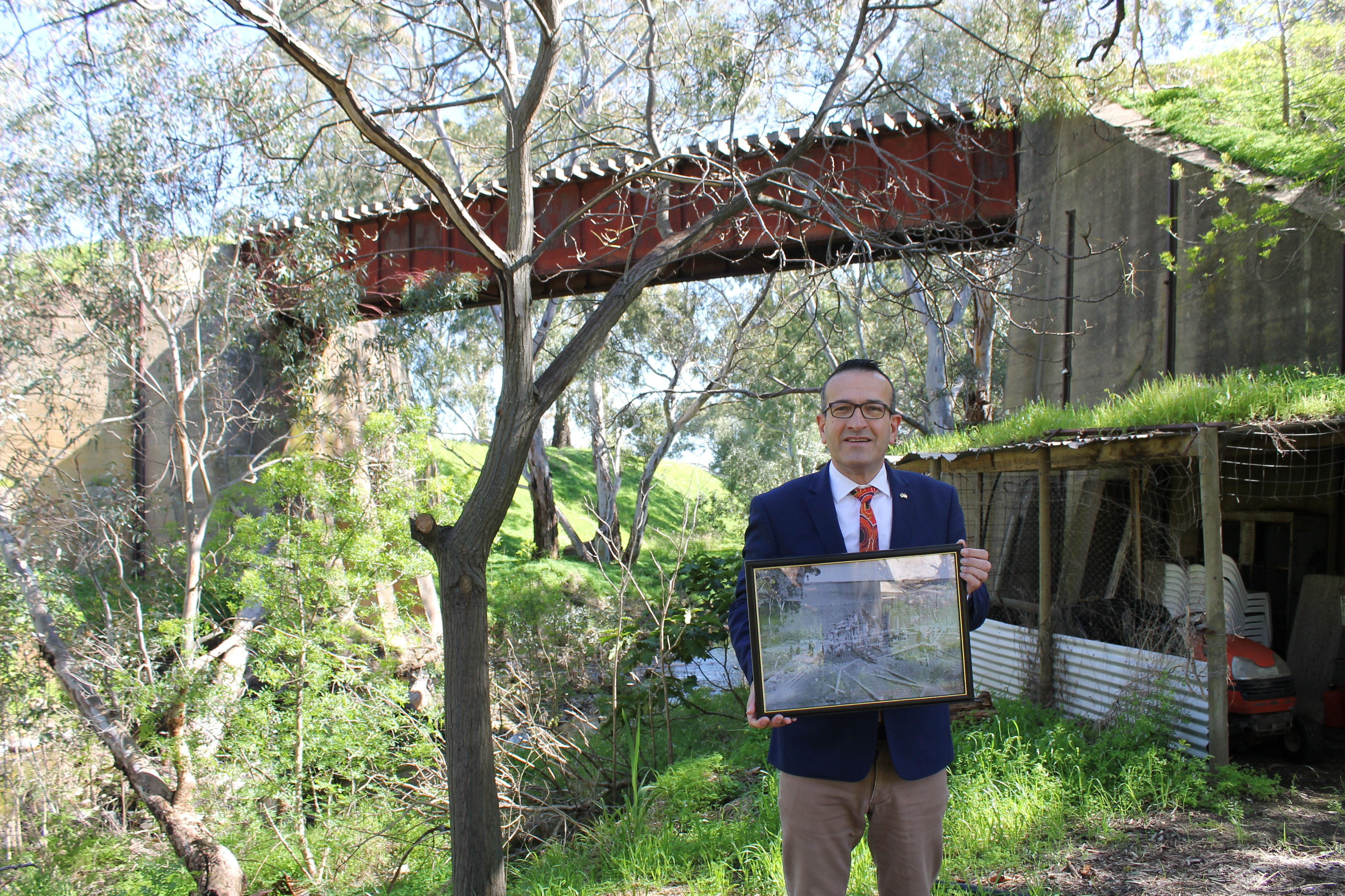 Tony Piccolo at the Jacob's Creek railway bridge with the photo taken during the original construction, which is part of the rail history exhibitions