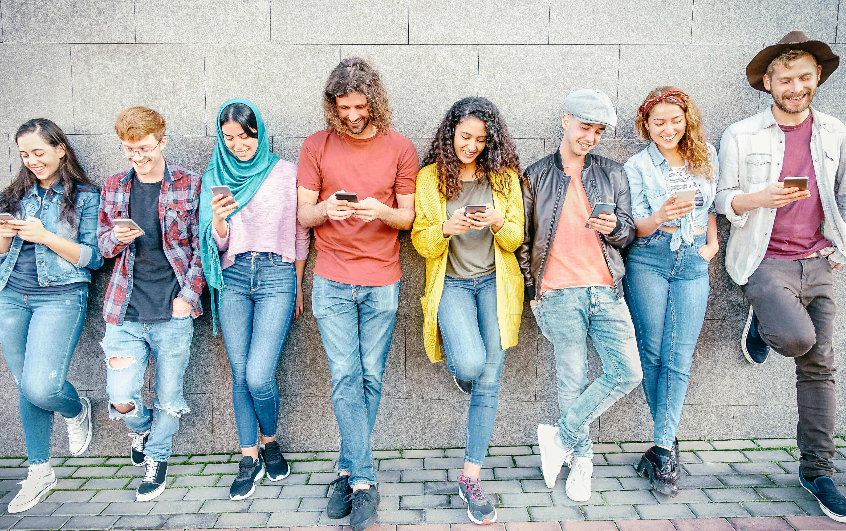a group of young people with smartphones on their hands