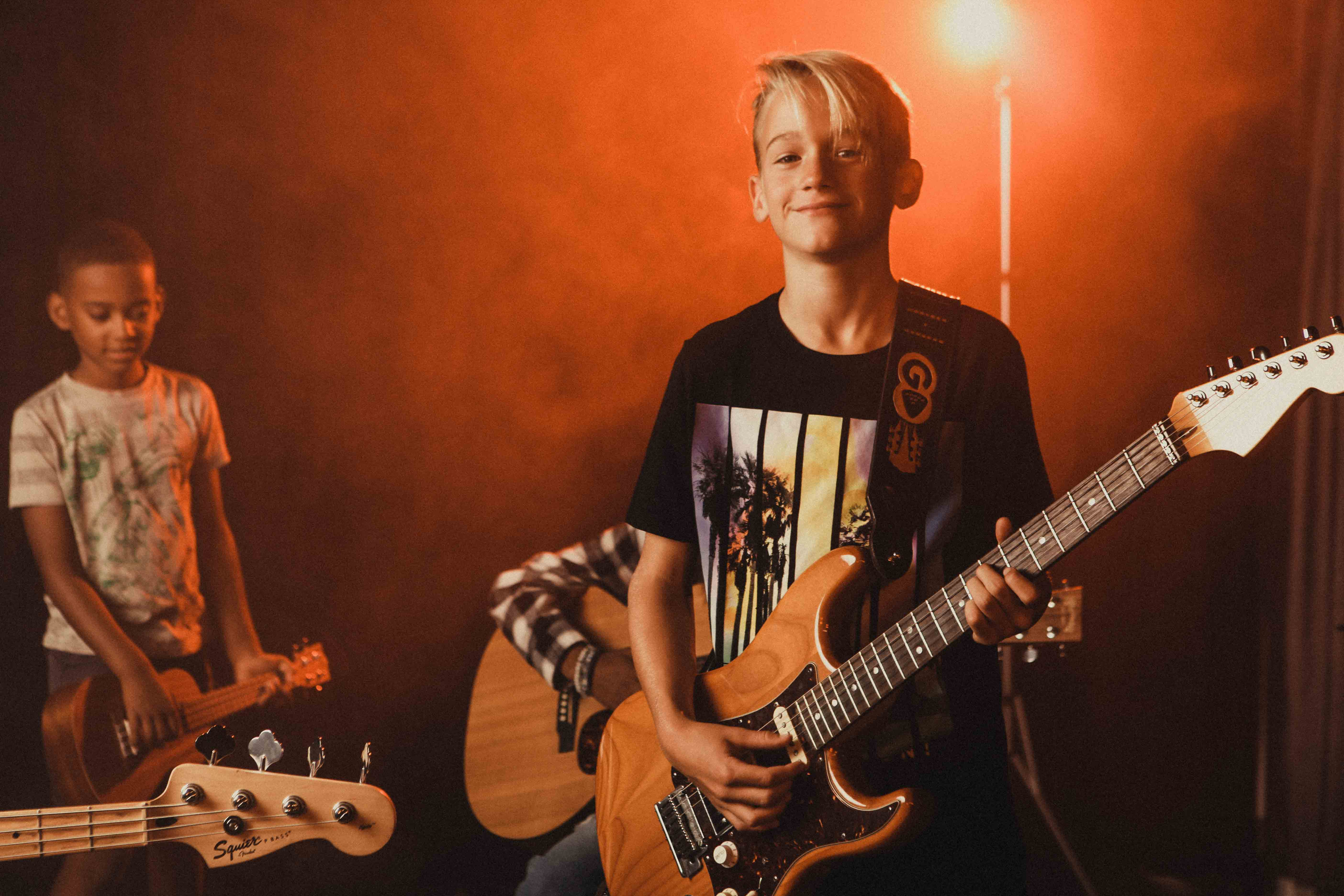 Kid with a bass guitar smiling with orange smoke and light behind them