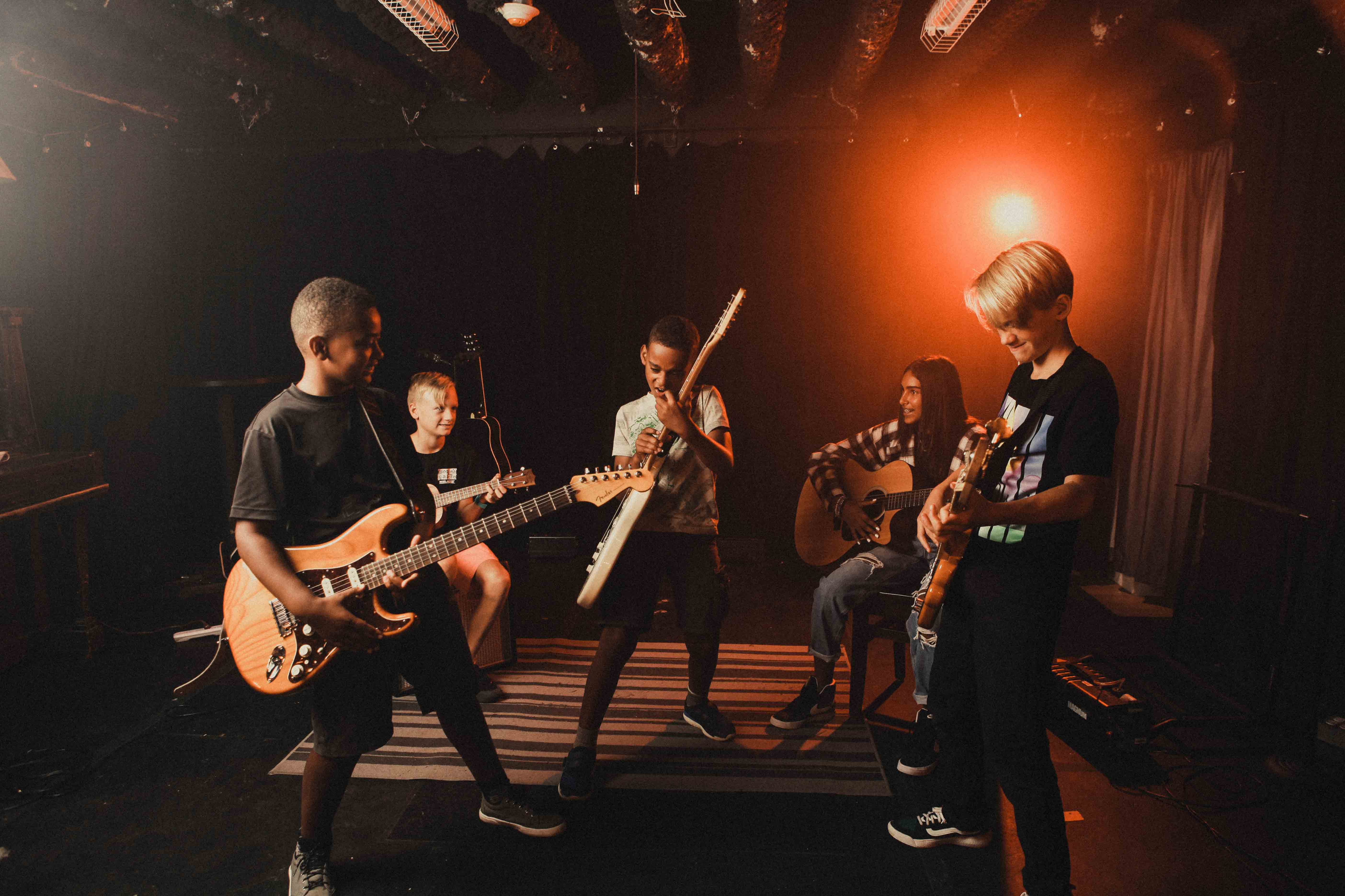 Kids playing guitars on a stage with a orange light in the background