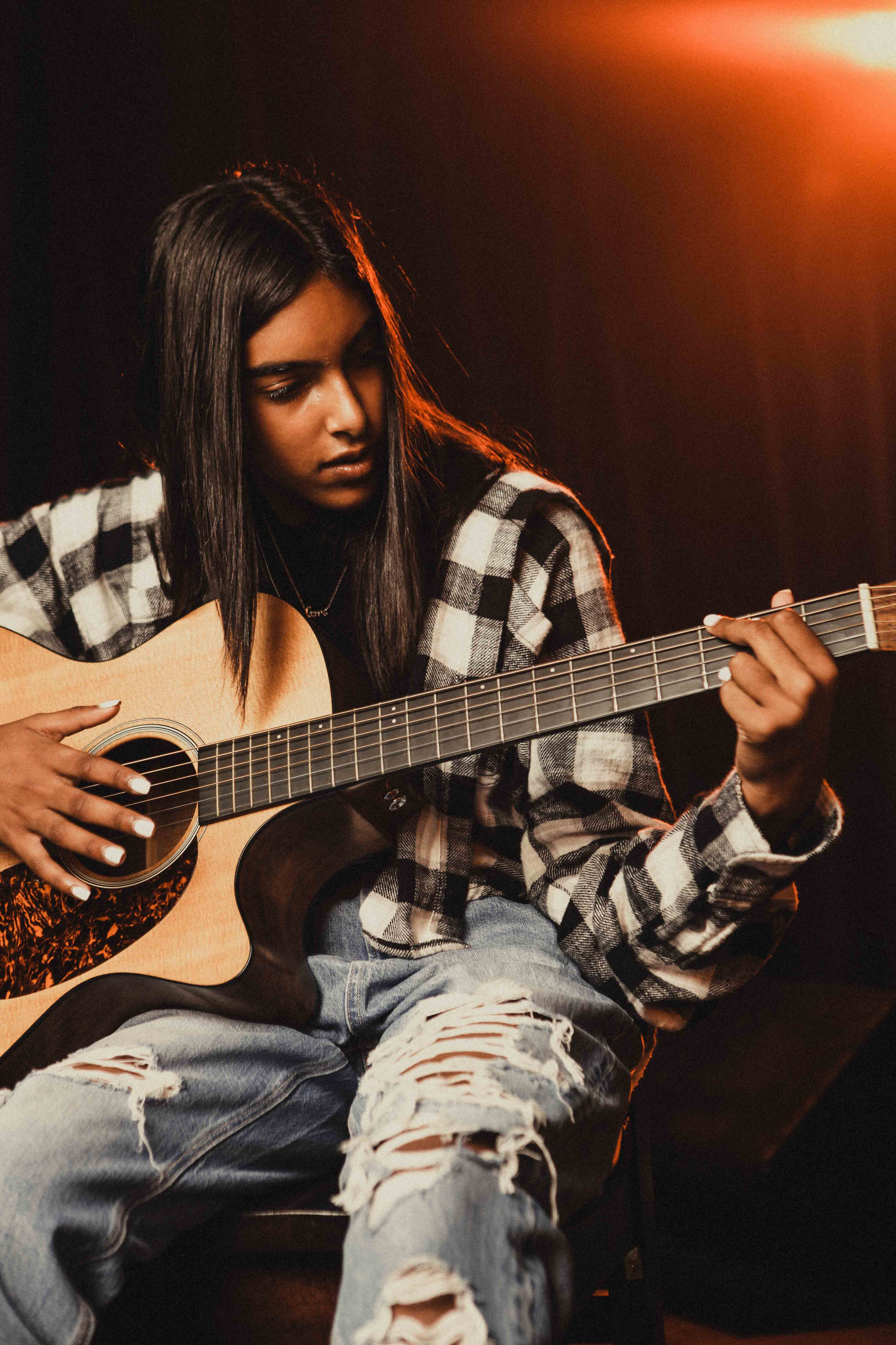 Photo of person playing an acoustic guitar