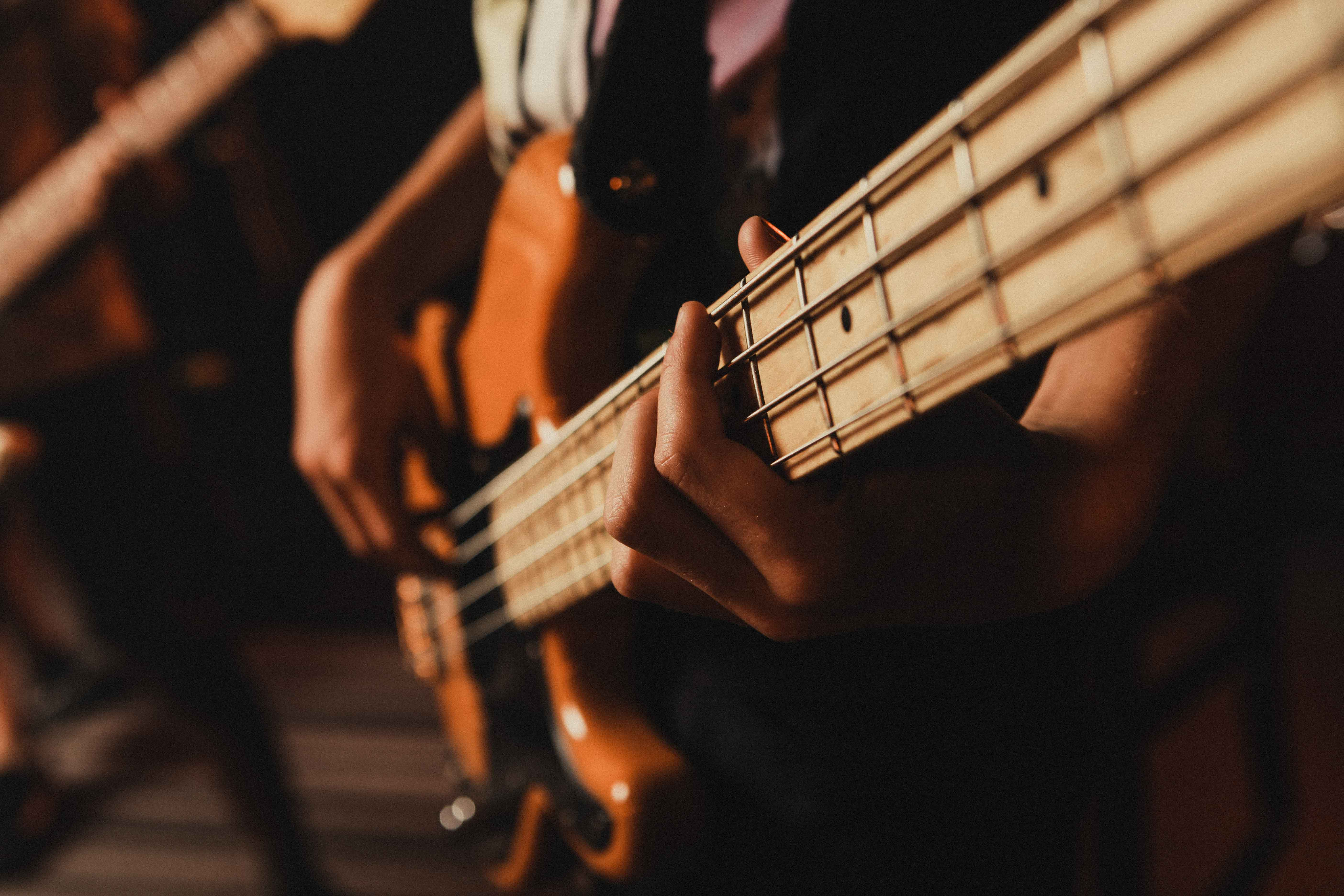 Close-up of fingers pressing notes on a bass guitar