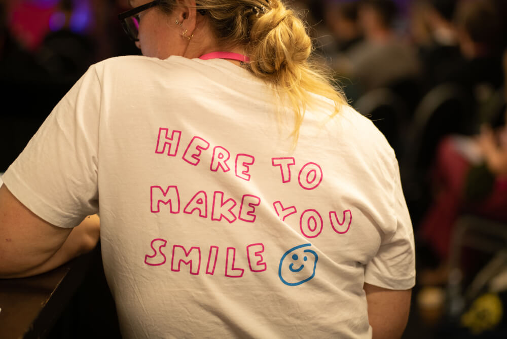 """UX New Zealand attendee wearing a shirt that says """"hear to make you smile"""""""