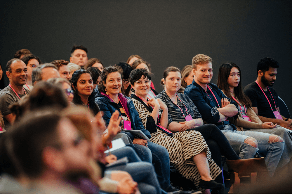 The crown smiling and laughing during a talk at UX New Zealand