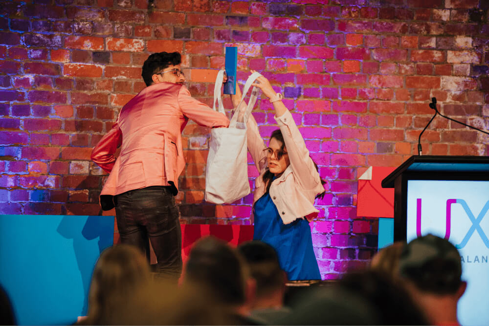 hosts up on stage selecting prize winners from a bag