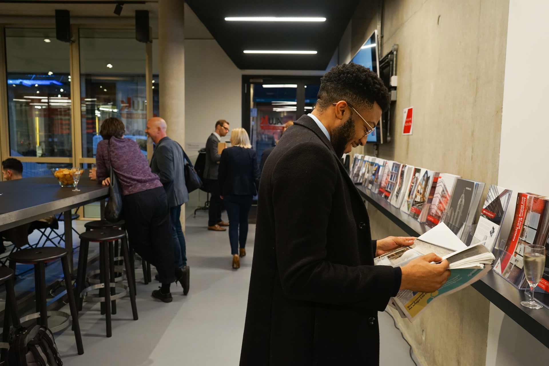 A man reading a brochure in the AluK Design Studio