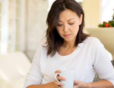 Woman holding coffee cup.