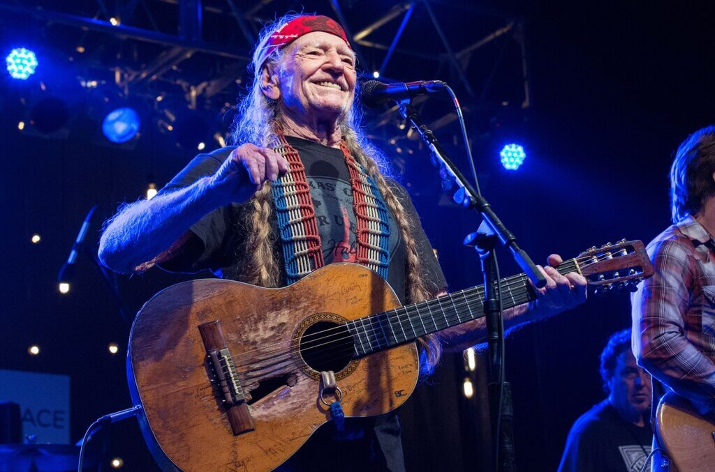 Willie Nelson playing a guitar