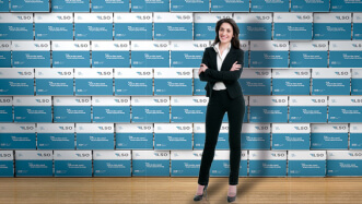 A woman in a black business suit in front of a wall of LSO boxes