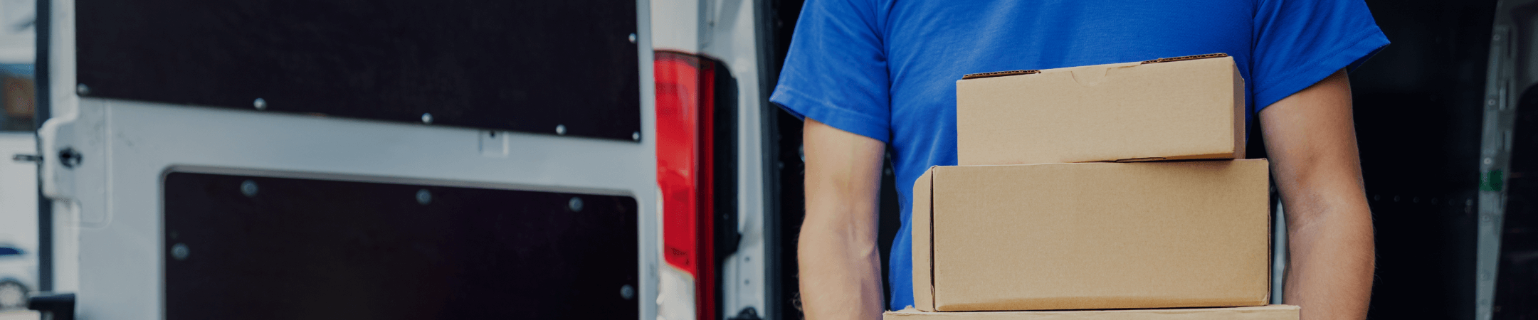 Delivery driver holding three brown boxes in front of a delivery van.
