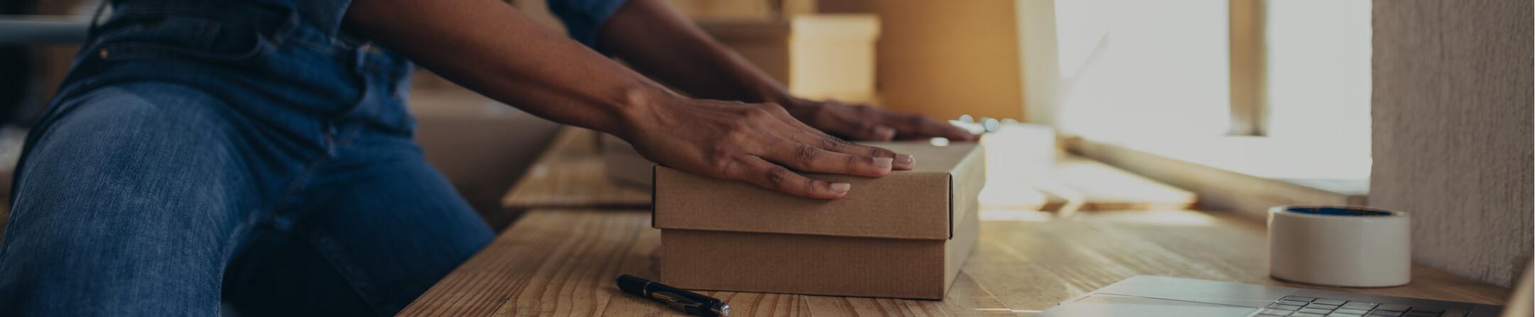 A person closing a brown box on a desk