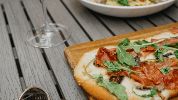 A pizza and a wine glass on a wood table