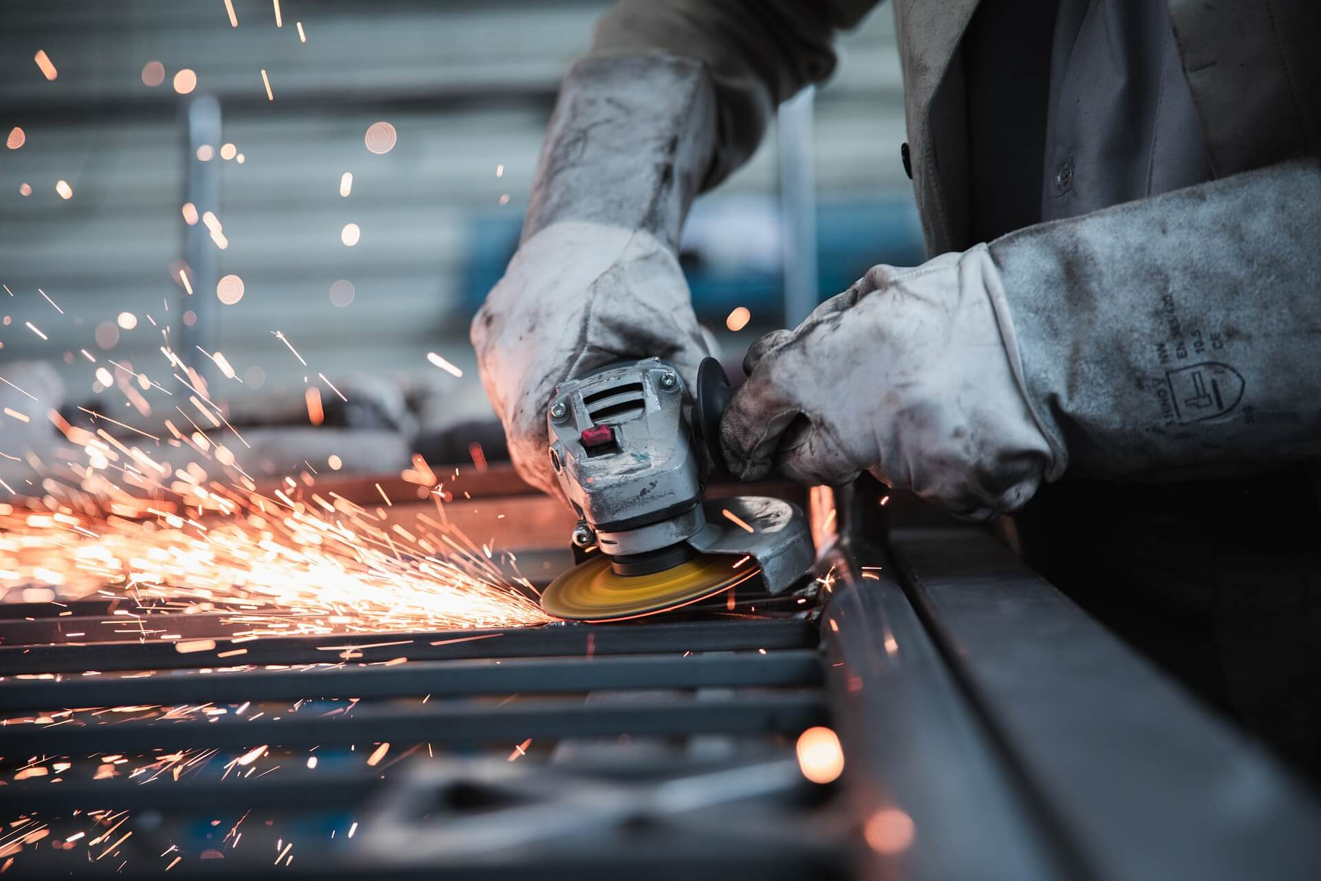 Worker with gloves sanding a metal structure and producing sparks