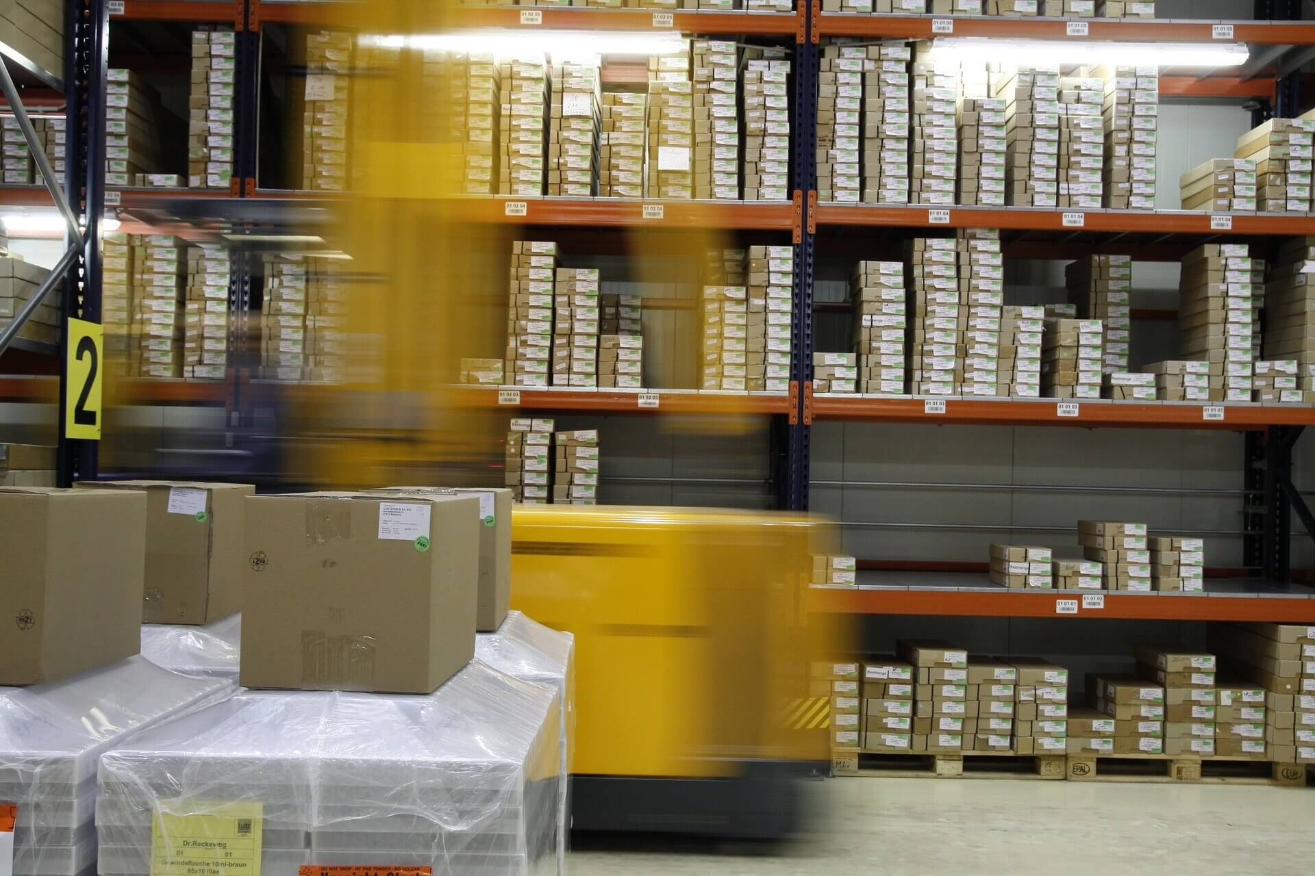 warehouse with shelves and different sized boxes on the shelves and a forklift moving through an isle.