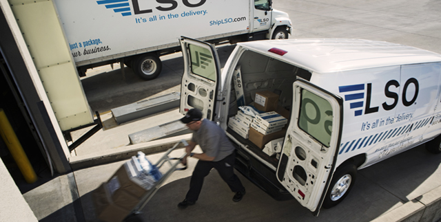 LSO driver with dolly loaded with packages behind an LSO delivery van with the back cargo doors open