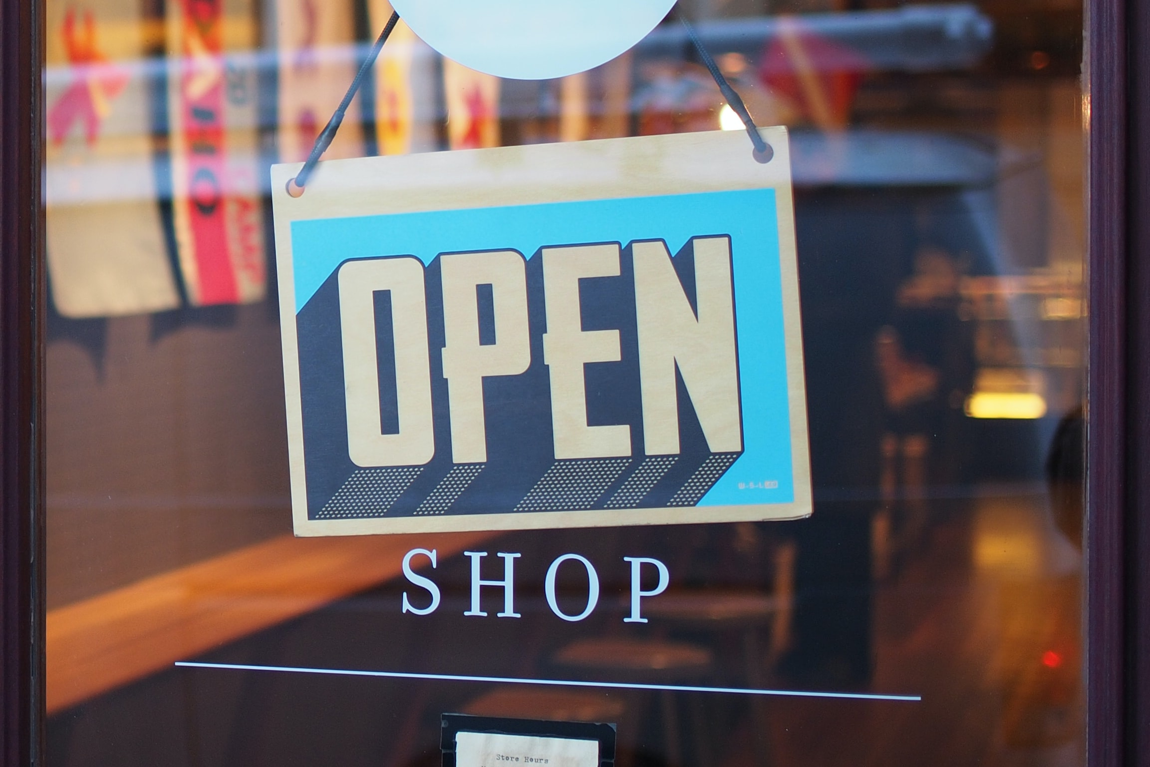 A storefront with a sign that says Open  and Shop