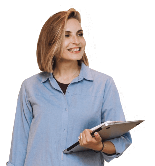 A smiling team member looking into the distance while holding a laptop and notebook.