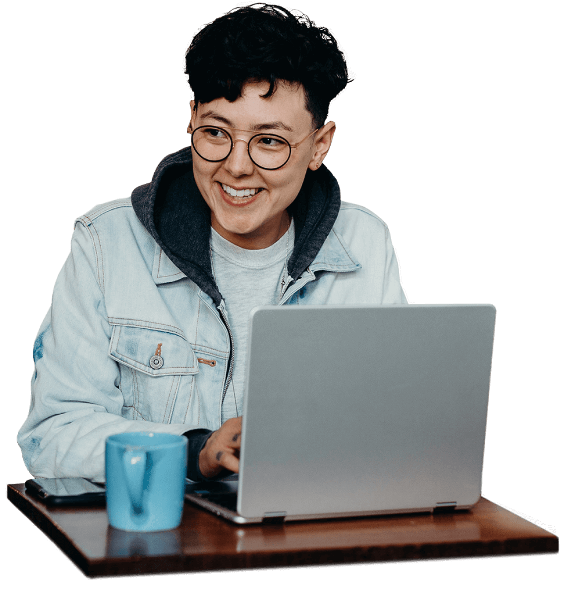 An engineering manager in a denim jacket looks up from their laptop with delight.