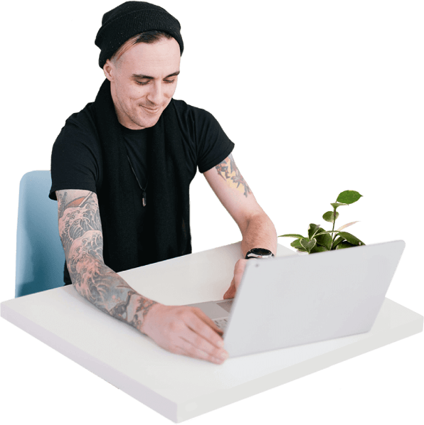 A software engineer with a detailed arm tattoo and wearing a beanie hat smiles as he works on his laptop.