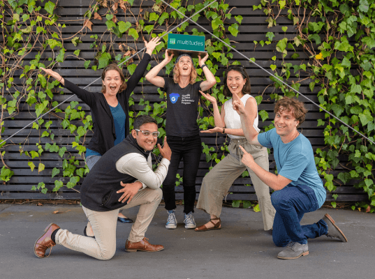 Multitudes Team members posing excitedly in front of a wall with green vines.