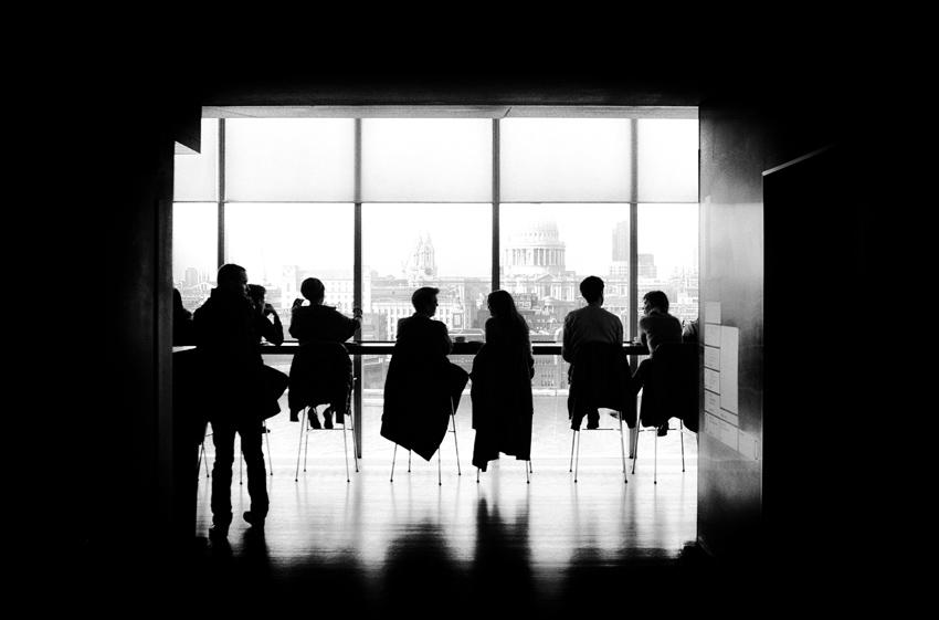Men Sitting in A Dark Room Infront Of Glass