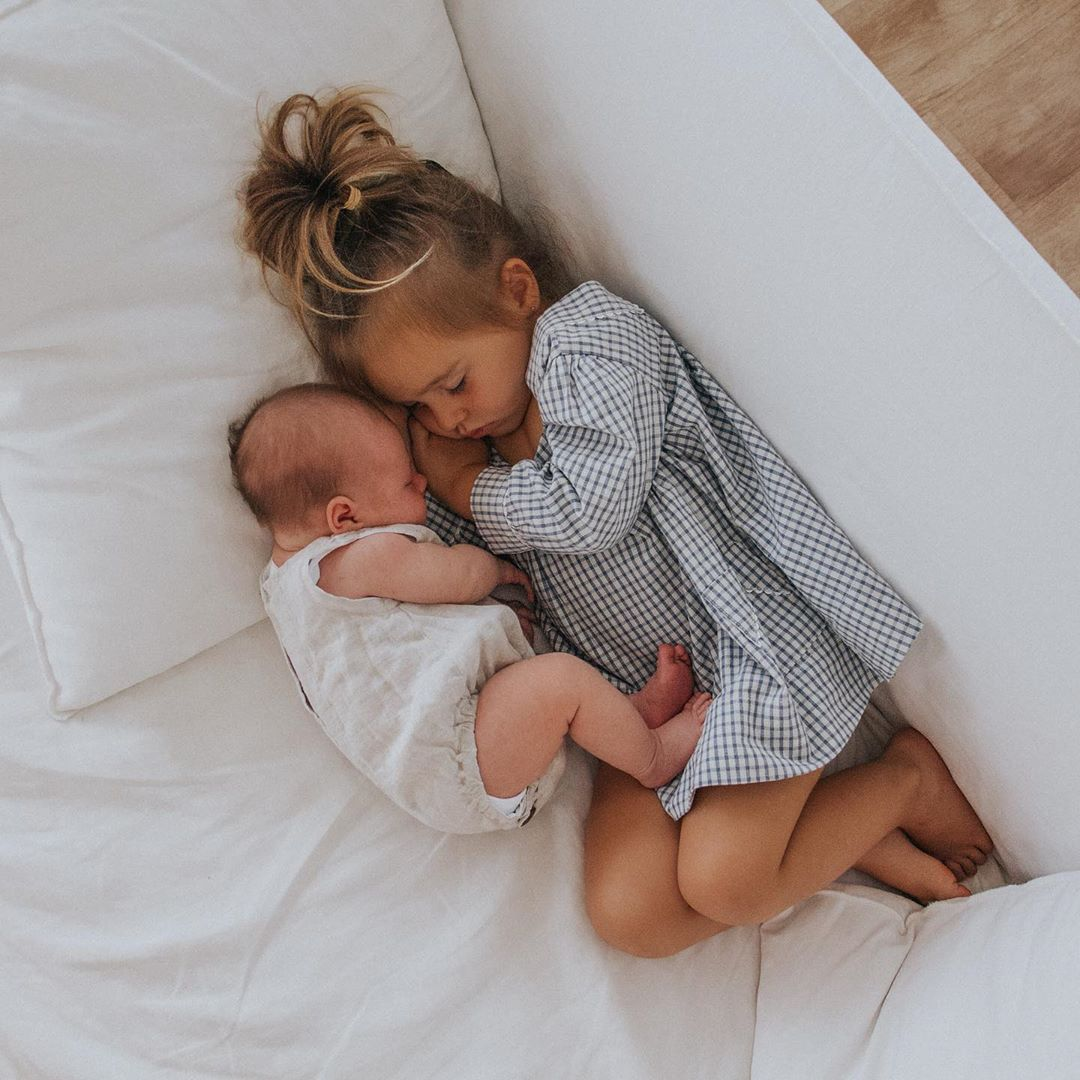 photo of a toddler and a small baby sharing a nap together