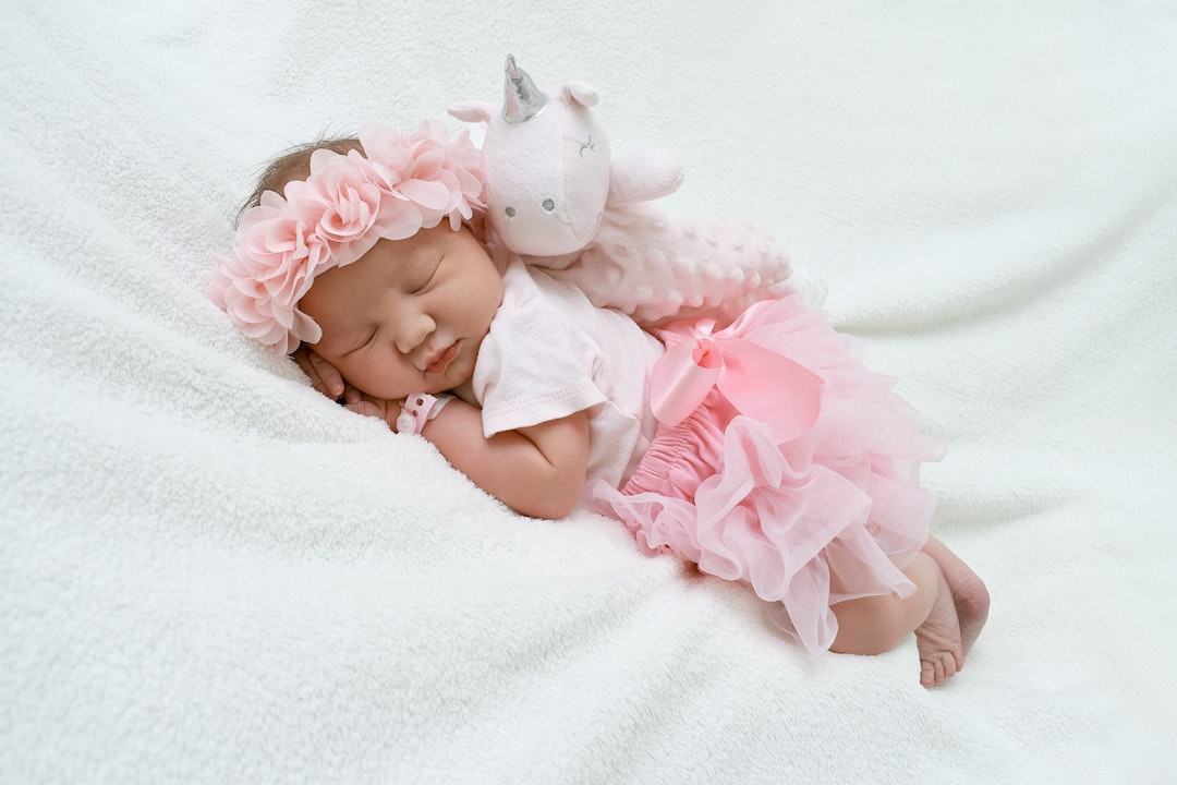 small baby in a pink outfit lying peacefully on a mat
