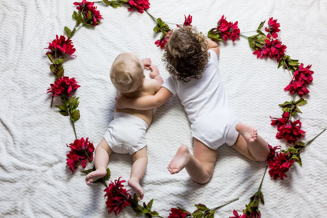 two small babies lying on a white sheet surrounded by roses in the shape of a heart