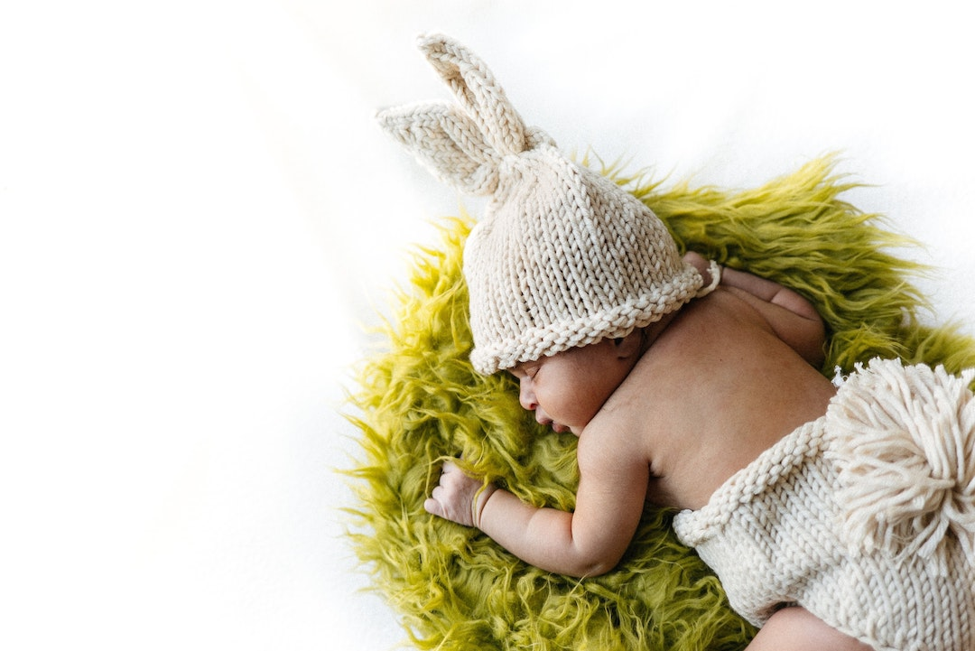 small baby in a tiny knitted easter bunny oiutfit lying on a green mat