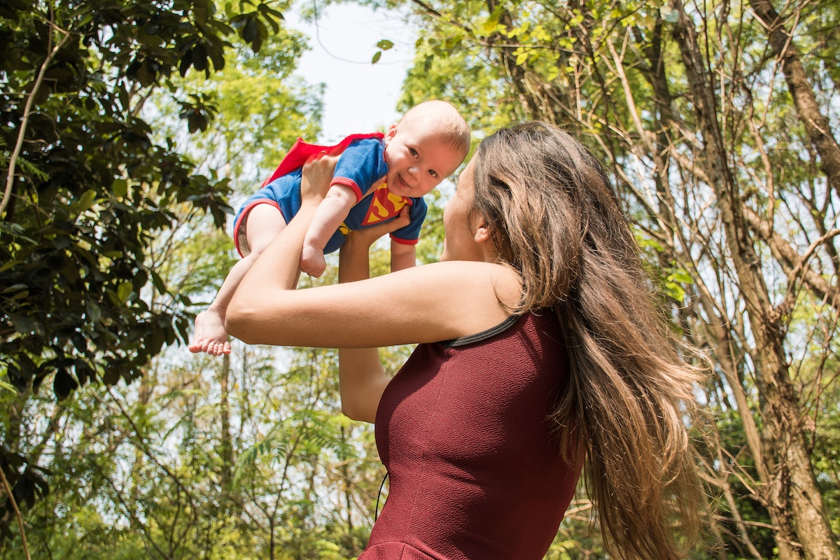 mother lifting her baby up in the air and the baby is wearing a superman outfit and costumes are a great idea for outdoor baby photography.