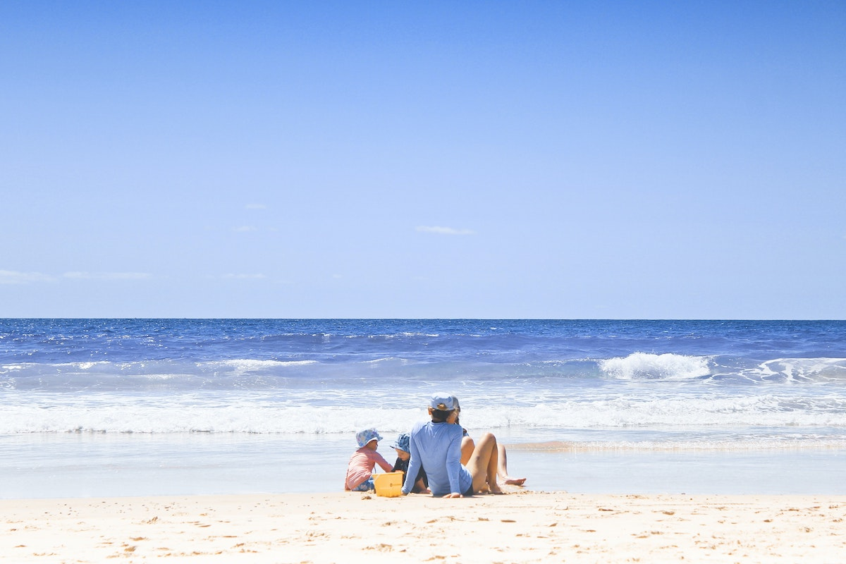 family on the beach in the gold coast with blue sies and small waves in the background