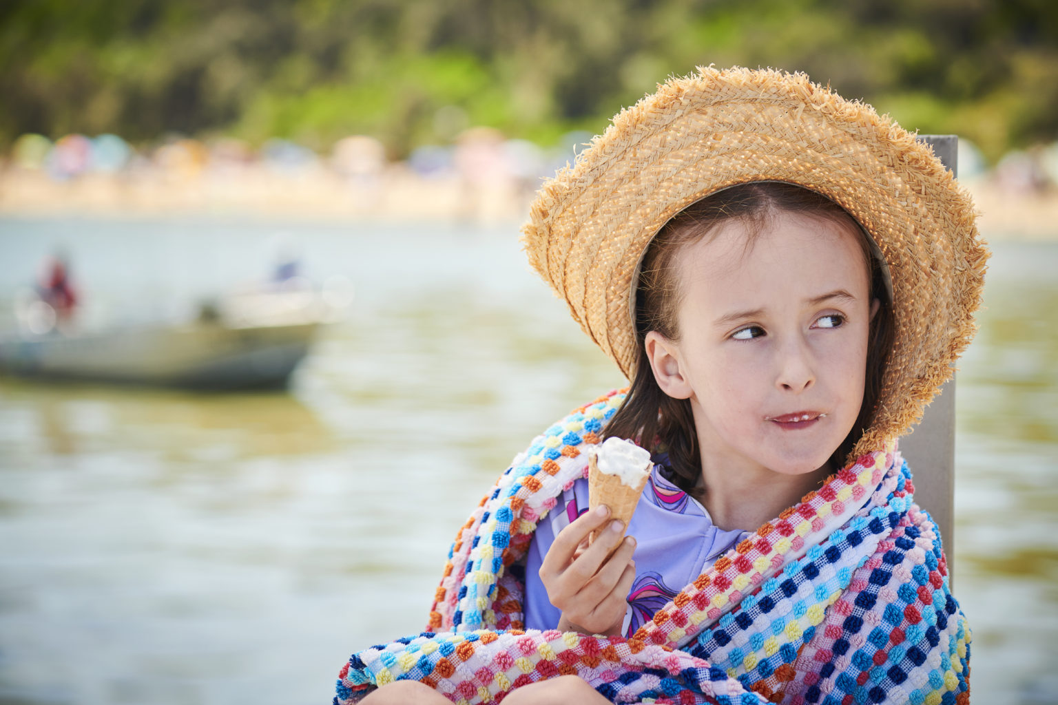 A young girl relaxing on the beach wrapped in a towel wearing a hat eating an icecream